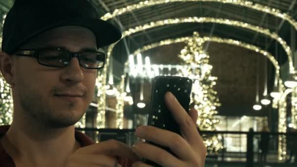 Mann dekoriert trägt Brille Schriftrollen app in seinem Handy in einem Weihnachten Einkaufszentrum. 4k erschossen