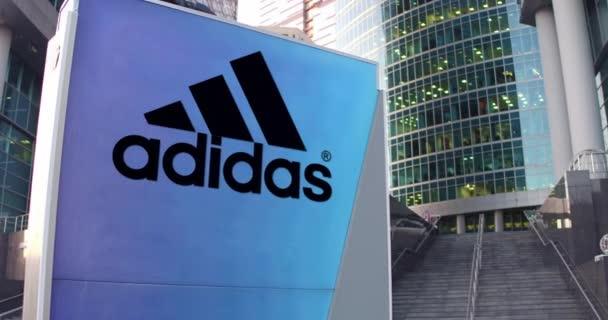 Pouliční nápisy deska s nápisem Adidas a logo. Moderní kancelářské centrum mrakodrap a schody pozadí. Redakční 3d vykreslování 4k