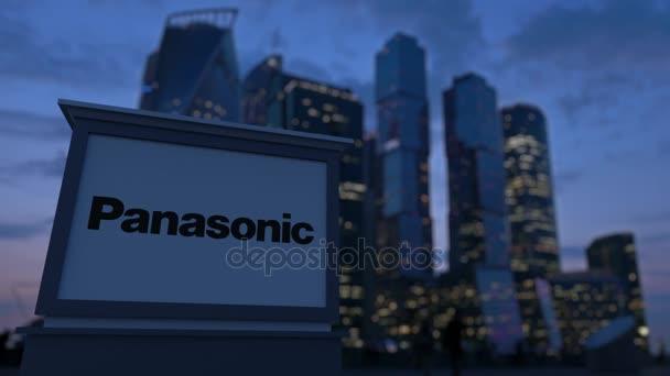 Pouliční nápisy deska s logem Panasonic Corporation ve večerních hodinách. Obchodní čtvrť mrakodrapů pozadí rozmazané. Redakční 3d vykreslování 4k