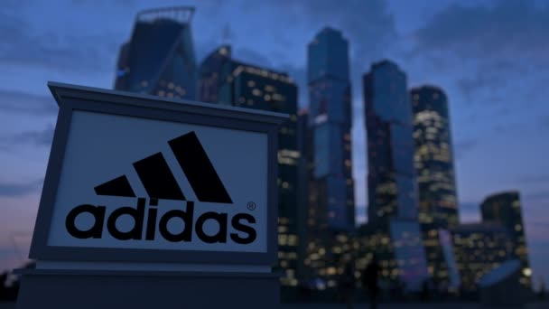 Pouliční nápisy deska s nápisem Adidas a logo ve večerních hodinách. Obchodní čtvrť mrakodrapů pozadí rozmazané. Redakční 3d vykreslování 4k