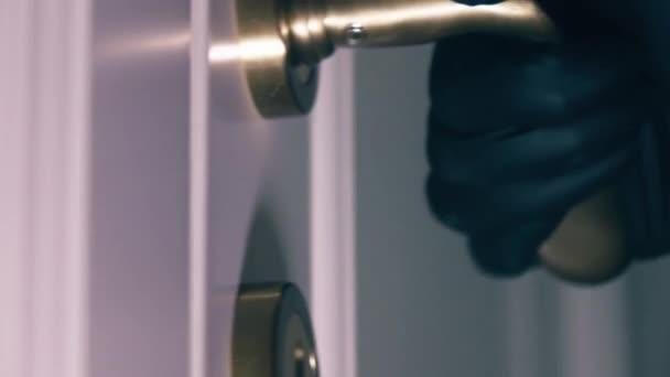 Neznámá osoba nosí černé rukavice se zavře a uzamkne dveře klíčem. Bezpečnost, soukromí, tajemství, zámek koncepty. 4 k close-up shot