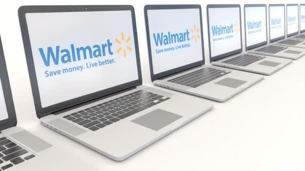 Moderní notebooky s logem Walmart. Počítač technika koncepční redakční 4k klip, bezešvé smyčka