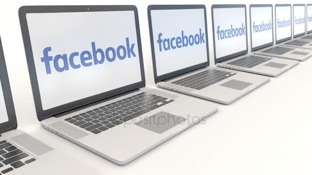 Moderní notebooky s logem Facebooku. Počítač technika koncepční redakční 4k klip, bezešvé smyčka