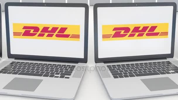 Notebooky s logem Dhl Express na obrazovce. Počítač technika koncepční redakční 4k klip, bezešvé smyčka