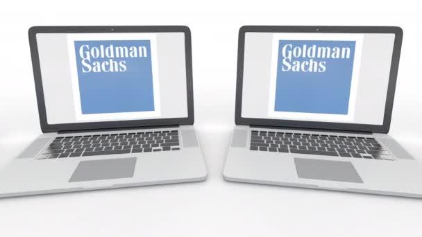 Notebooky s logem Goldman Sachs Group, Inc. na obrazovce. Počítač technika koncepční redakční 4k klip, bezešvé smyčka