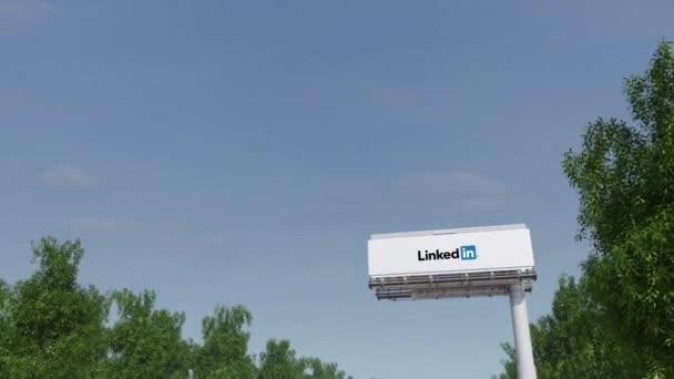 Driving towards advertising billboard with LinkedIn logo. Editorial 3D rendering 4K clip