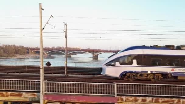 Varšava, Polsko - 27 března 2017. Letecký snímek sledování moderní osobní vlak, pohybující se na železničním mostě přes řeku. 4k video
