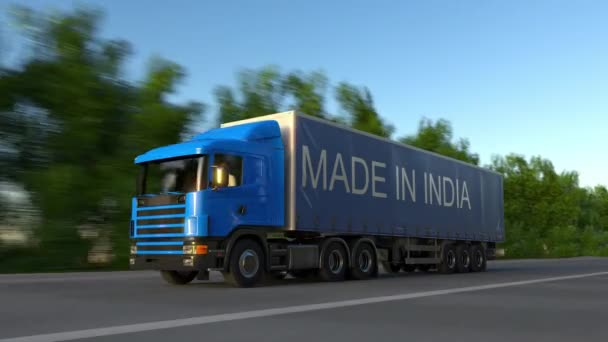 Speeding freight semi truck with MADE IN INDIA caption on the trailer  Road  cargo transportation  Seamless loop 4K clip