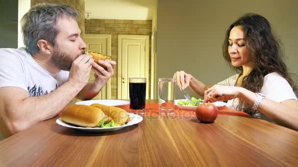 Mladý bělošský muž a žena doma jíst hotdogs a hlávkový salát. Nekvalitní potraviny versus zdravé stravovací koncept. 4k video
