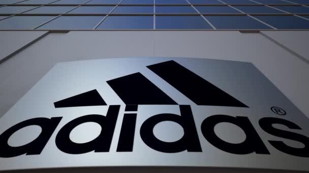 Venkovní značení deska s nápisem Adidas a logo. Moderní kancelářská budova. Úvodník 3d vykreslování