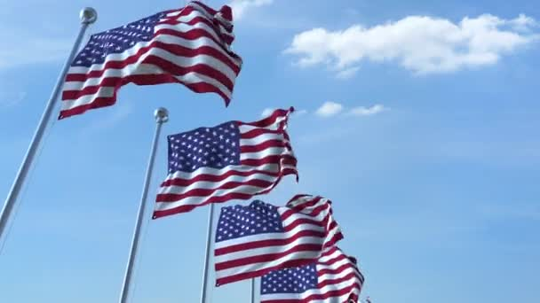 Row of waving flags of the United States agaist blue sky, seamless loop