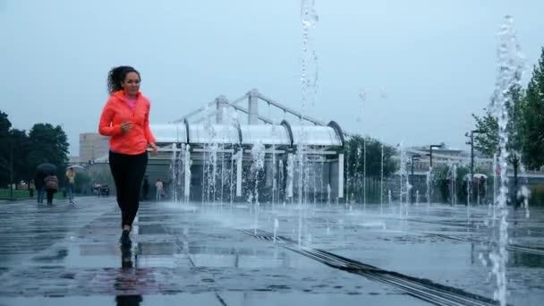 Mladá Smíšené rasy atletické ženské běžec běží v dešti u city parku fontány, super slow motion výstřel
