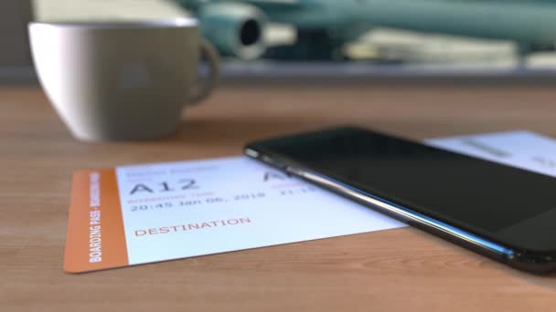 Boarding pass to Abidjan and smartphone on the table in airport. Travelling to Ivory Coast conceptual animation