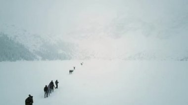 Aerial shot of unrecognizable people hiking on the frozen mountain lake Sea Eye in the snow, Poland