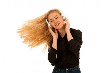 Beautiful young woman listens to the music on headphones and dan