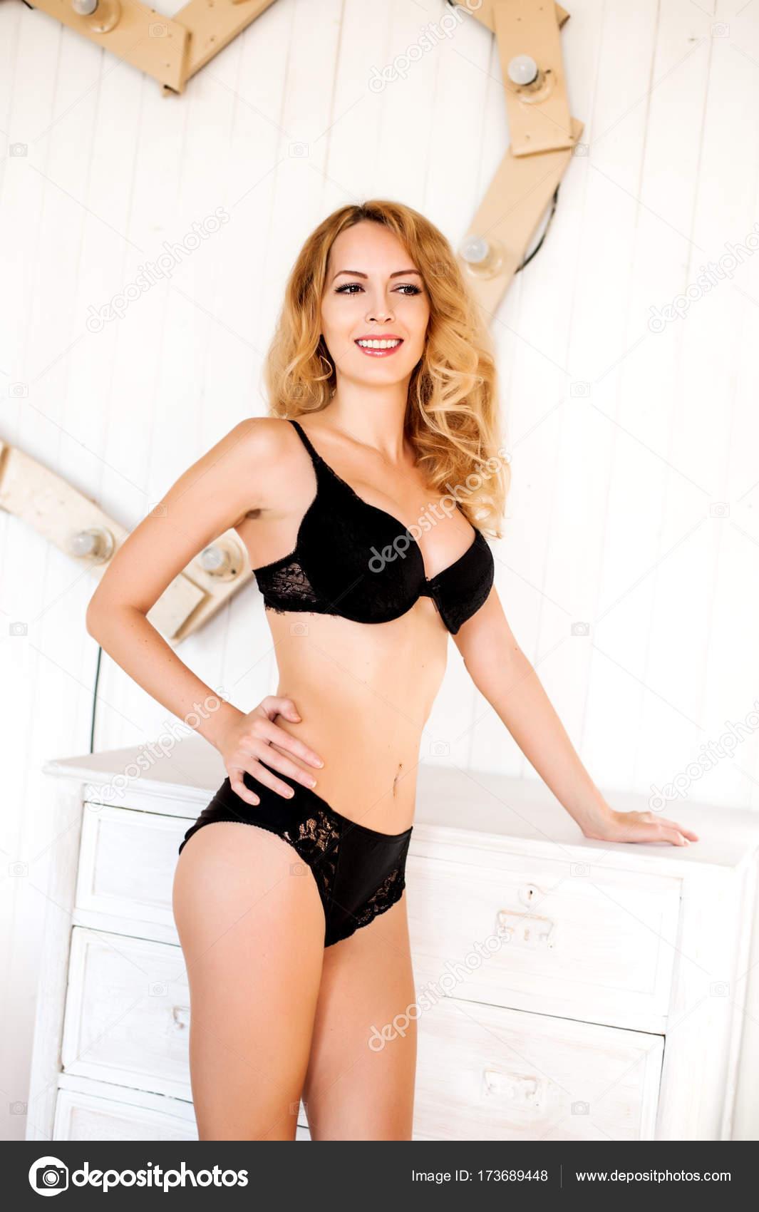 8aac2bafc Lingerie sexy linda modelo - loira jovem com perfeita figura vestindo  calcinha preta e sutiã no quarto branco e sorriso — Fotografia por ...