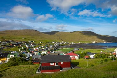 SORVAGUR, FAROE ISLANDS, DENMARK - JULY 09, 2019: Traditional faroese village with harbor beach and picturesque houses. Sorvagur. stock vector