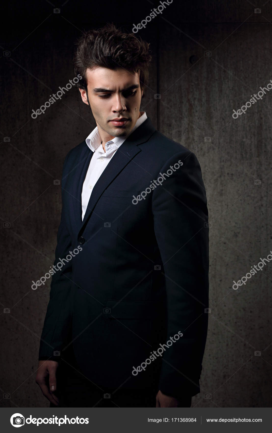 75e14836 Sexy handsome male model posing in blue fashion suit and white style shirt  looking down on dark shadow background — Photo by nastia1983