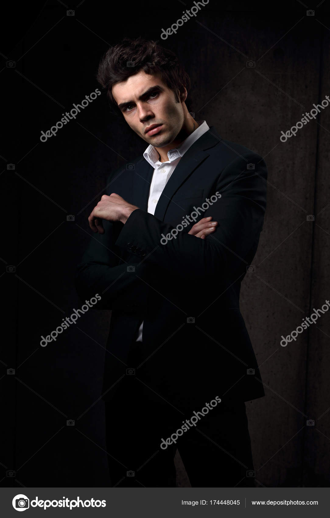 50386a80 Handsome male model posing in fashion suit and white style shirt looking on dark  shadow background.