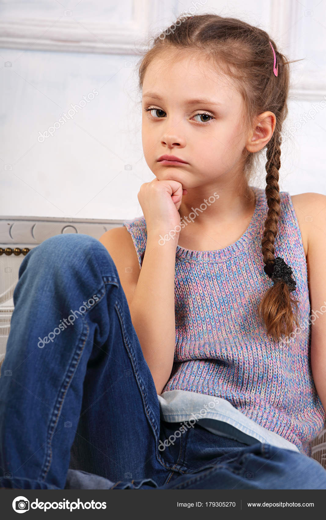 beautiful thinking cute kid girl sitting on the bench in blue je