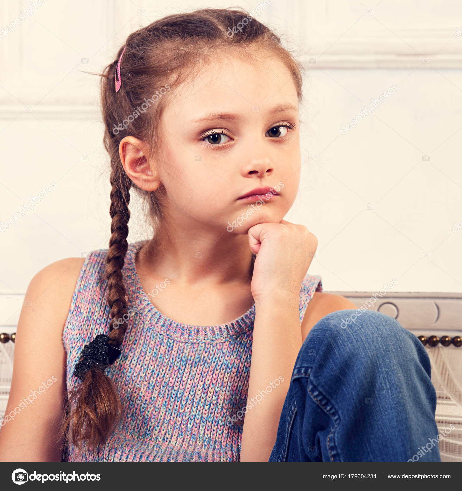 48d0b2fc5 Beautiful calm thinking unhappy kid girl sitting on the bench in blue jeans  and fashion blouse looking serious. Studio toned closeup portrait — Photo  by ...