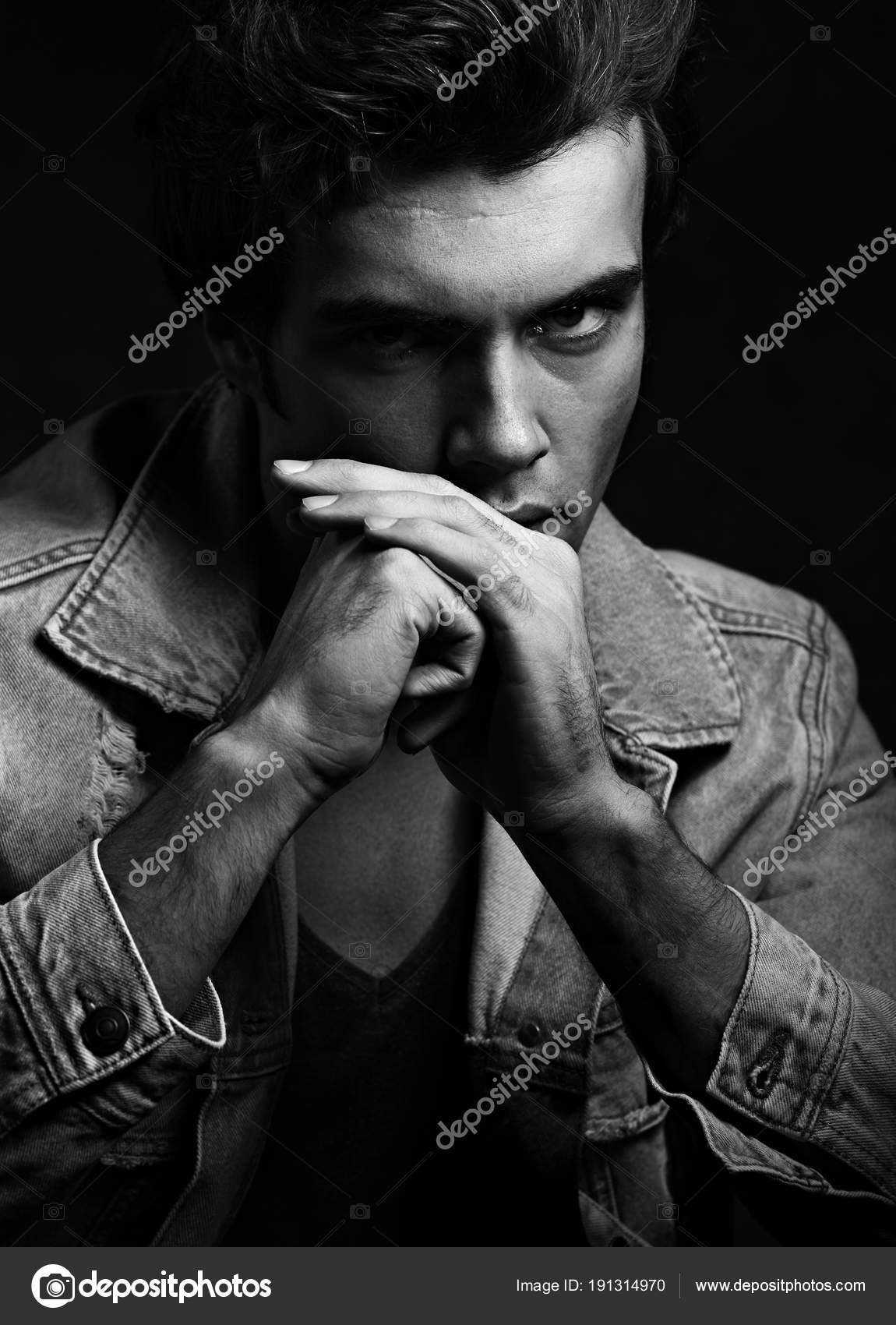 Handsome thinking male model posing in fashion blue jeans jacket looking on dark shadow background closeup black and white portrait photo by nastia1983