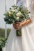 Elegáns esküvői csokor fehér és rózsaszín virágokkal a menyasszony kezében
