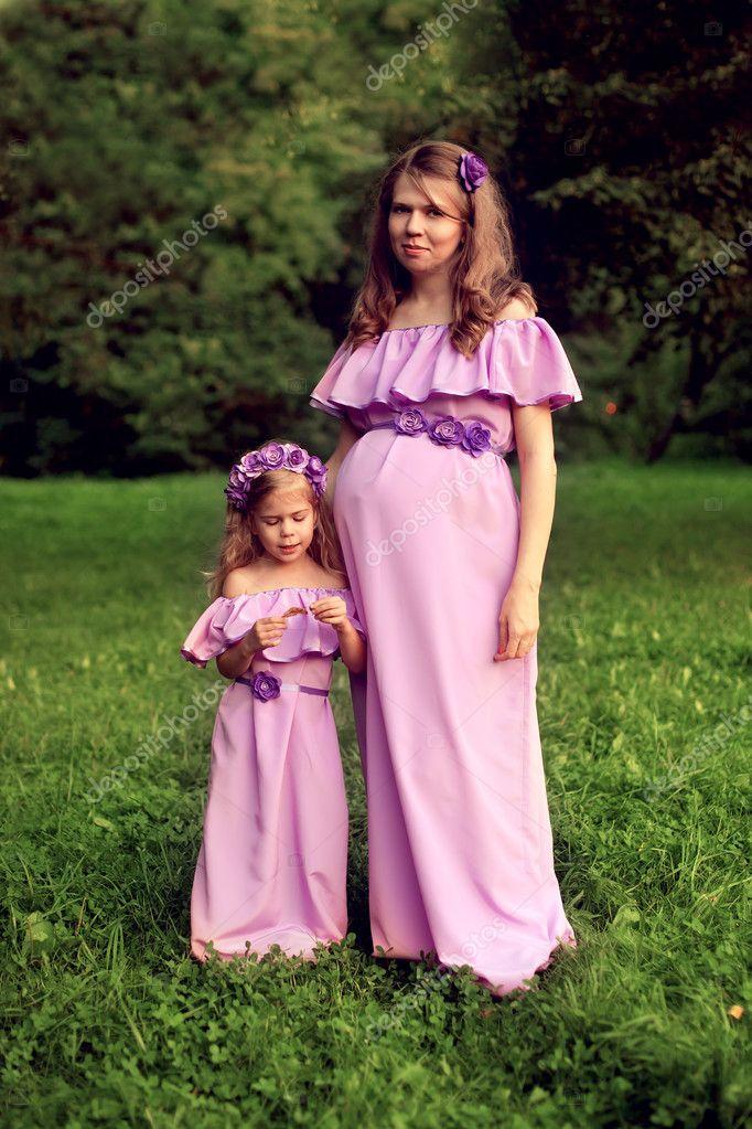 Madre embarazada e hija en idénticos vestidos lilas posando i — Foto ...