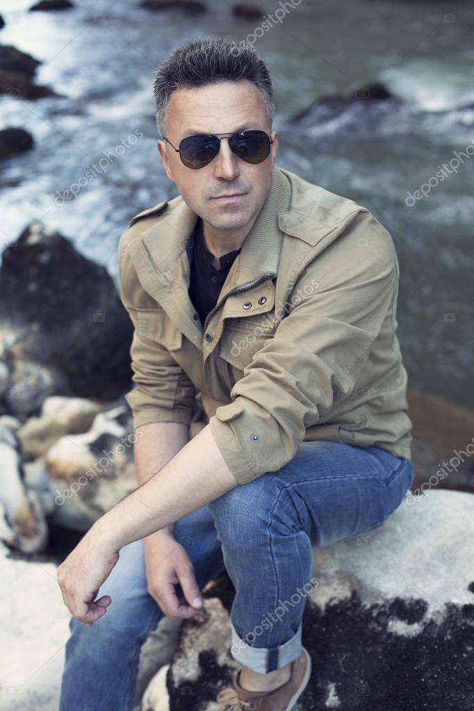 attractive man sitting on rocks
