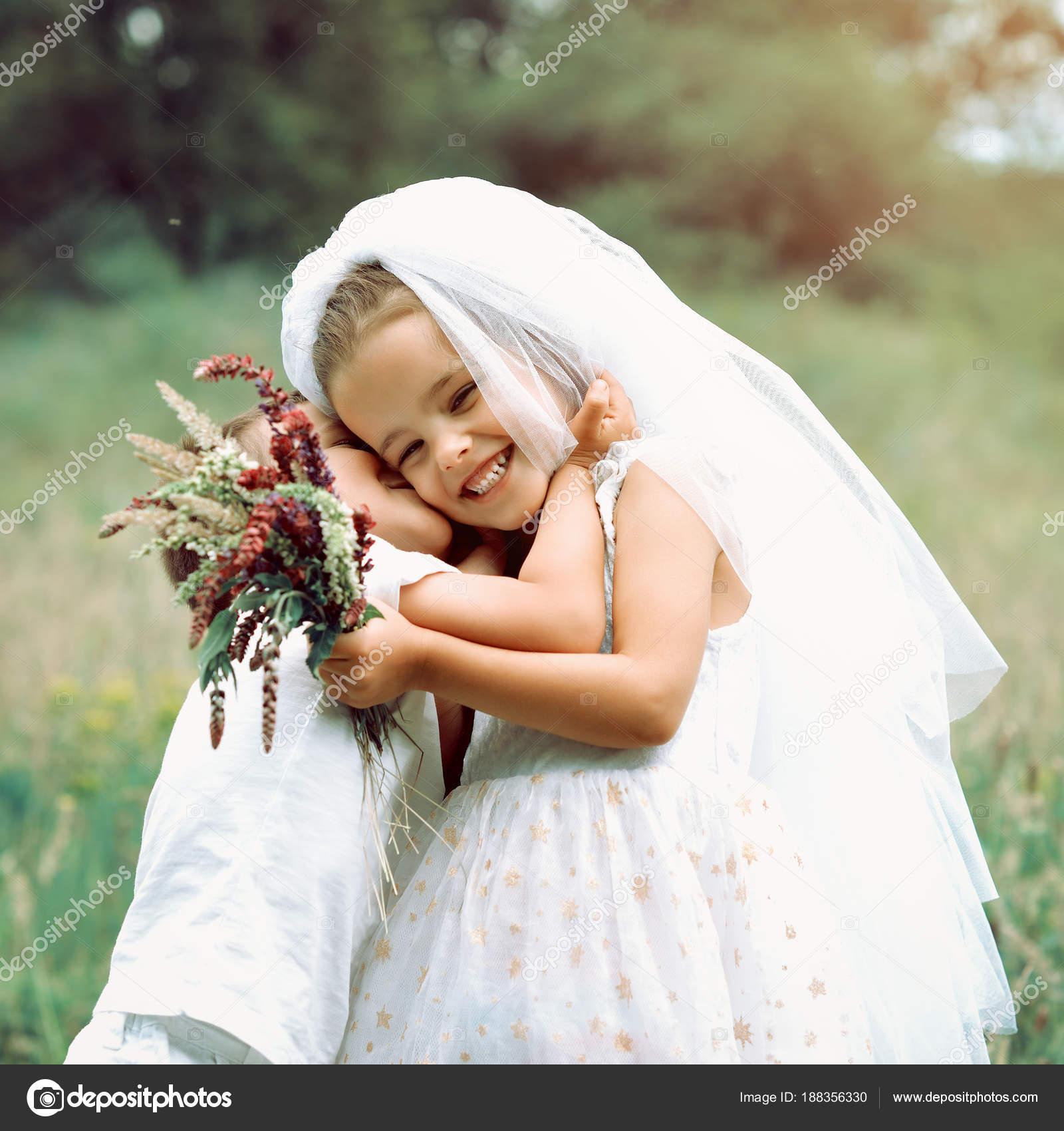 0832e28aa75b Τα παιδιά σαν νεόνυμφοι. Μικρό αγόρι γαμπρός φιλάει τον νεαρό κορίτσι στο φόρεμα  νύφη άσπρη και νυφικό πέπλο