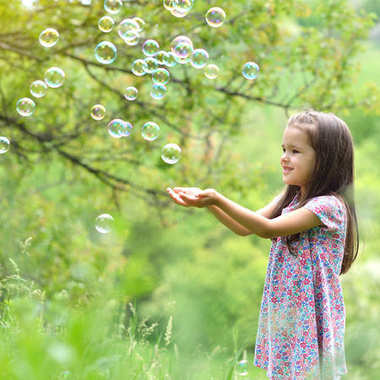 Cute little girl on a forest glade among lush vegetation and around fly soap bubbles. Kid wih soap bubbles over nature outdoor. stock vector
