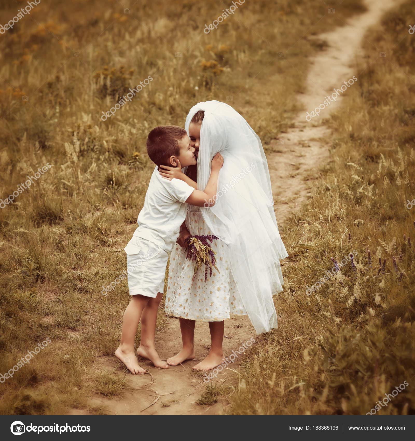 73e84af46fb9 Νέοι Νύφη και ο γαμπρός παίζοντας υπαίθριο γάμο το καλοκαίρι. Τα παιδιά σαν  νεόνυμφοι. Μικρό κορίτσι στο φόρεμα νύφη άσπρη και νυφικό πέπλο φιλιά μικρό  ...