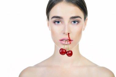 Young beautiful woman with ripe cherry bleeding nose. Anti-glamo