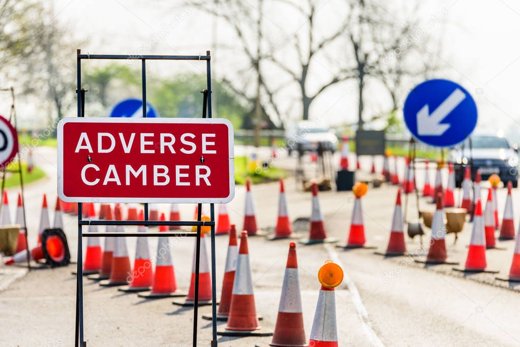 Adverse Camber Roadworks sign on UK motorway with cones