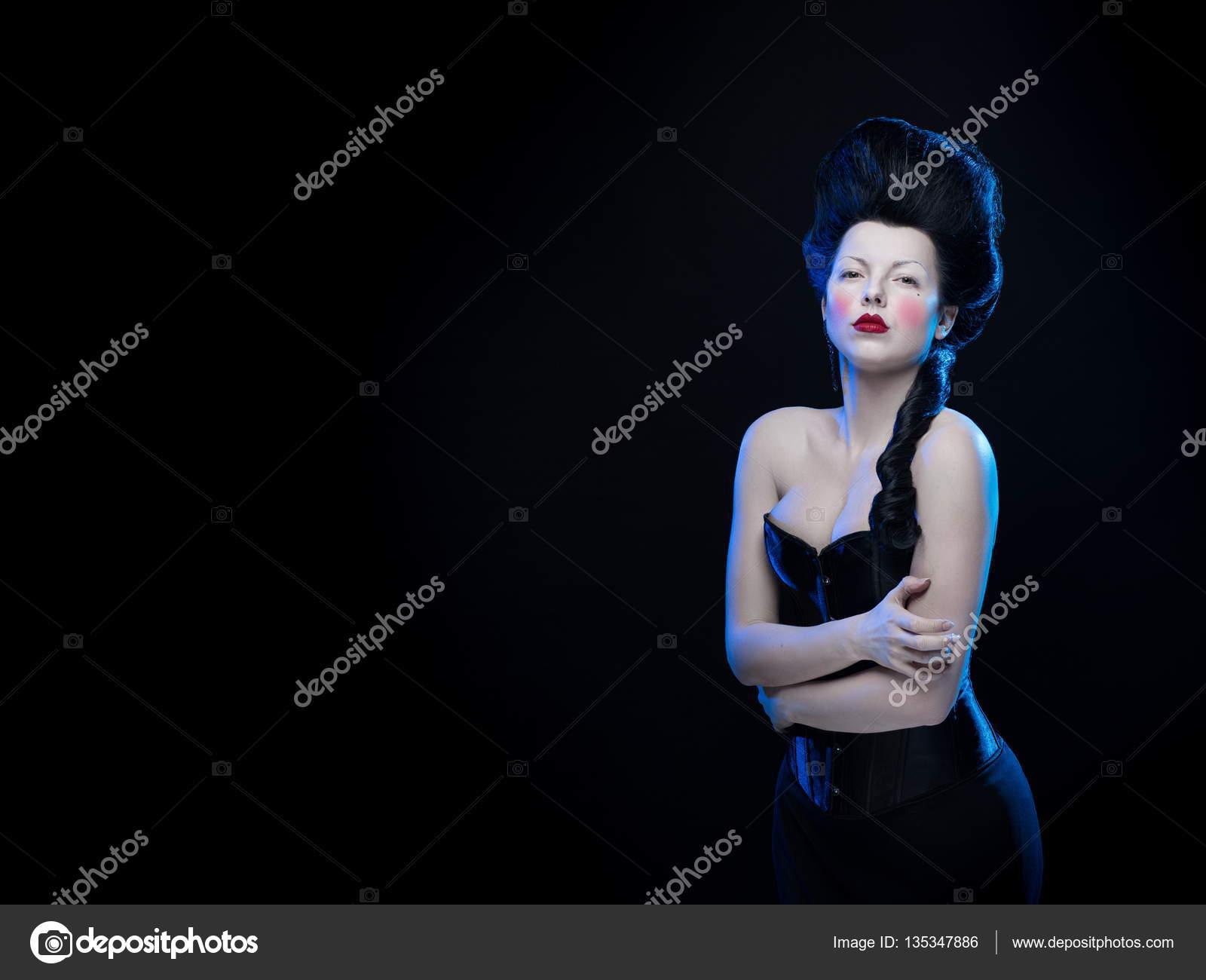 Donna bruna con i capelli alti e un corsetto in vecchio ...