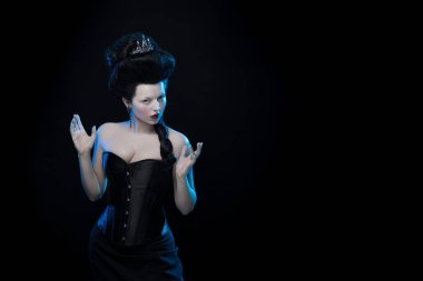 brunette woman with high hair, a tiara and a corset in old style