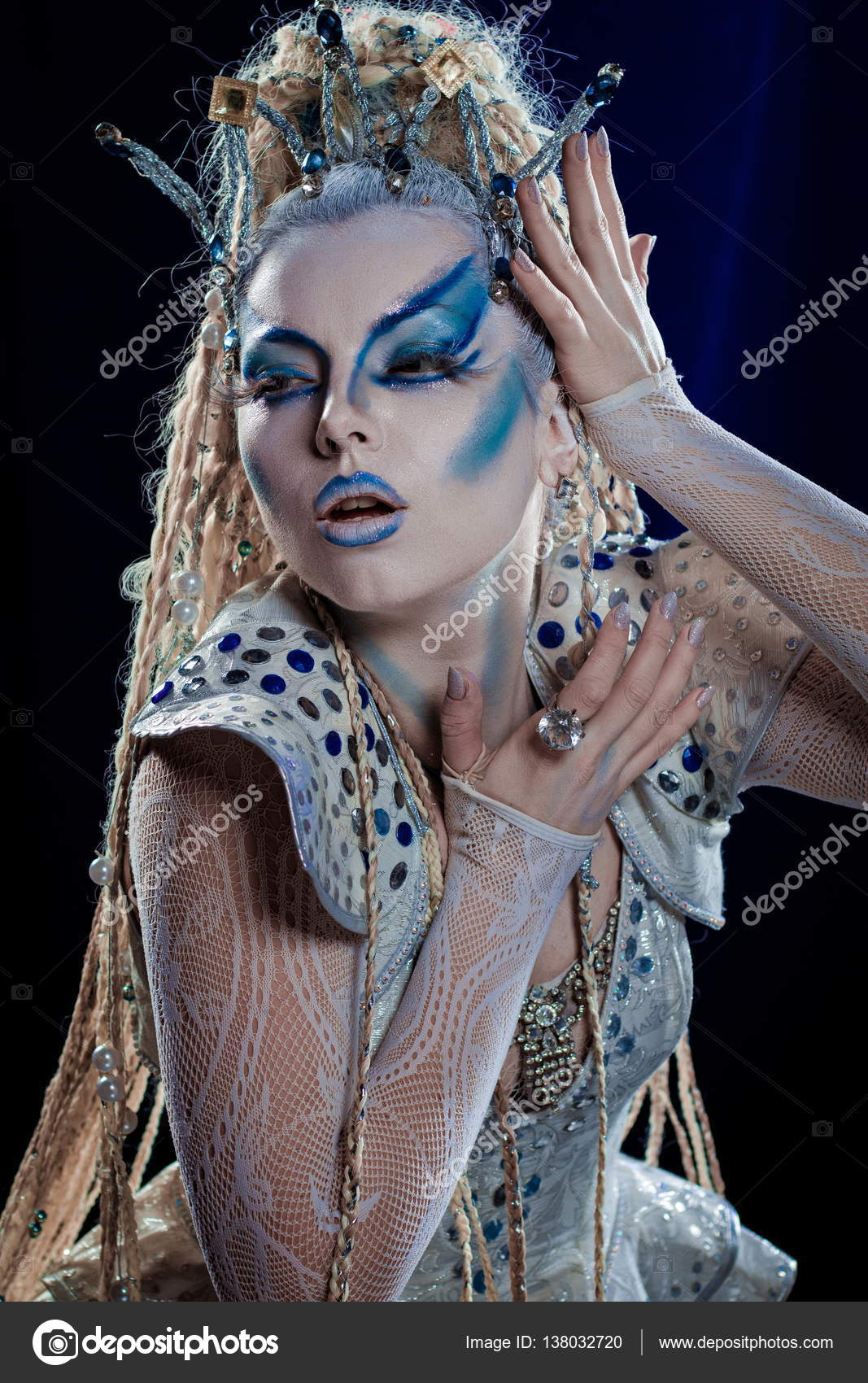 Emotional actress woman in makeup and costume of the Snow Queen in the  blue-black
