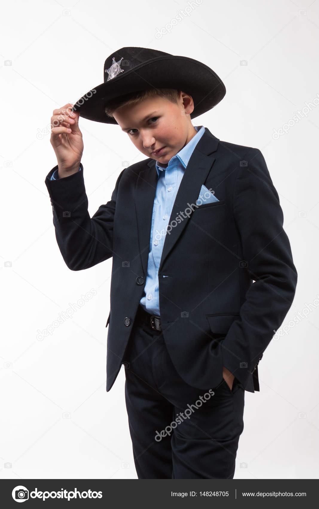 Adolescente muchacho en un traje y un sombrero negro sobre un fondo blanco  — Foto de Kozlik 1ca2c491178