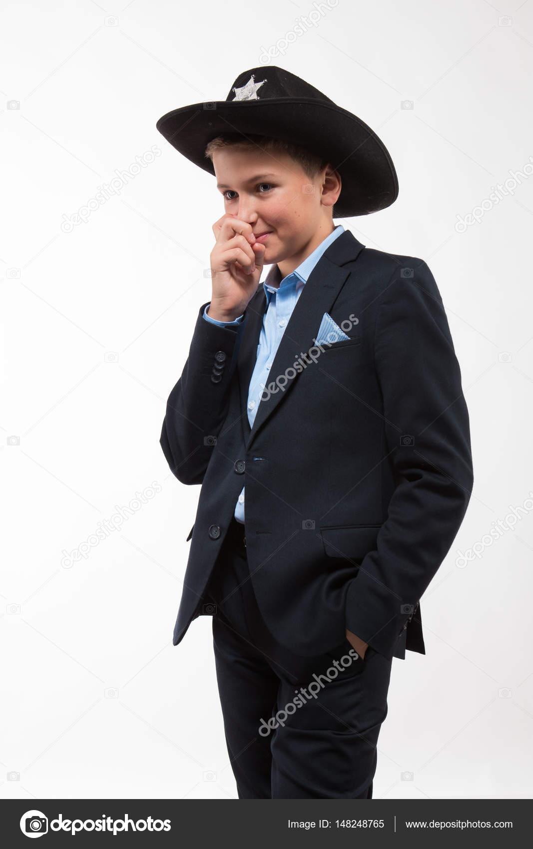 Adolescente muchacho en un traje y un sombrero negro sobre un fondo blanco–  Imagen de Archivo 2ca41589307