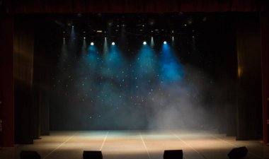 The stage of the theater illuminated by spotlights and smoke from the auditorium