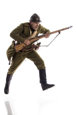 Male actor in uniform and helmet ordinary soldier of Russian army during World War I posing, jumping and running on white background in studio.