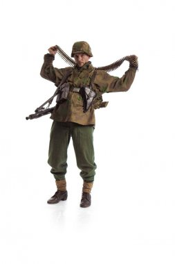 Man actor in the movie role of an old military man  with a MG 42 machine gun posing against white background