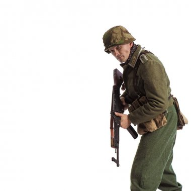 Man actor in the movie role of an old military man  with a machine gun posing against white background