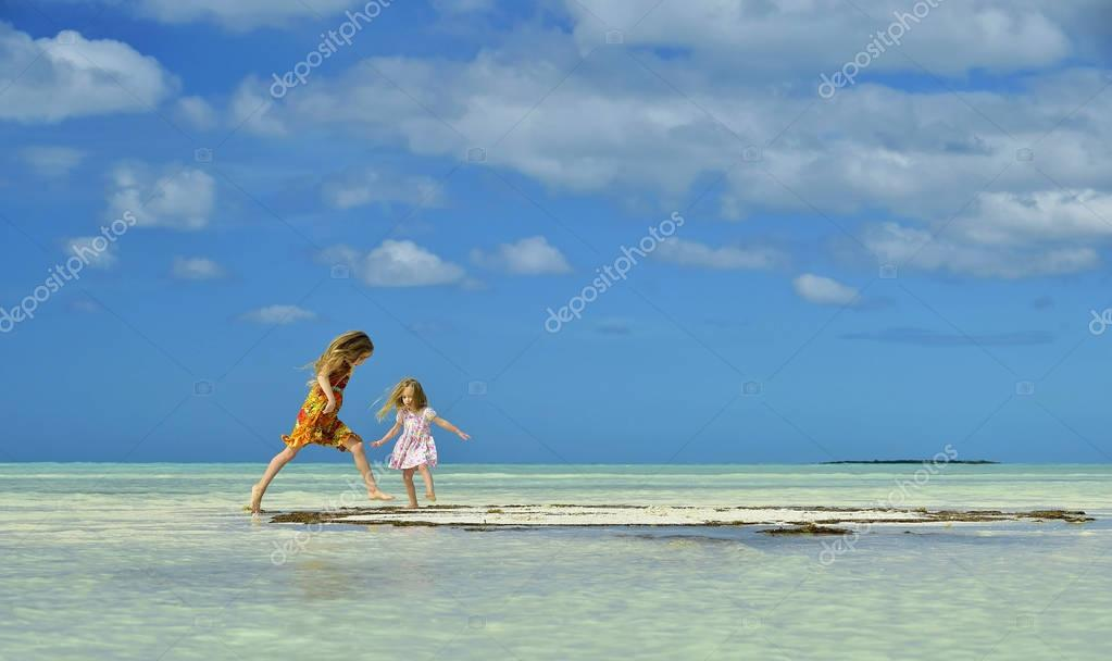Cute little girls on sandy beach in sunset light. Cuba. Caya Coco.