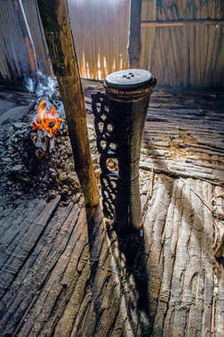 Ritual drum Asmat tribe at the fire in a ceremonial man's house of Asmat tribe. Asmat Village, Asmat province, Indonesia