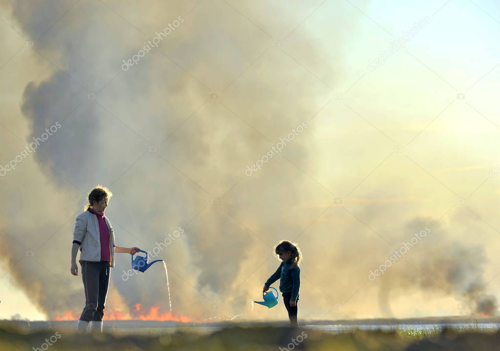 Mother and little daughter extinguish the fire from the watering can. Burning reeds on the shore of the lake, wildfire