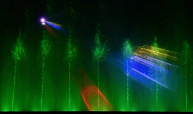 Colorful water fountains. Beautiful laser and fountains show. Large multi colored decorative dancing water jet led light fountain show at night. Dark