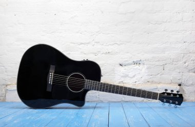 Musical instrument - Black acoustic guitar brick background