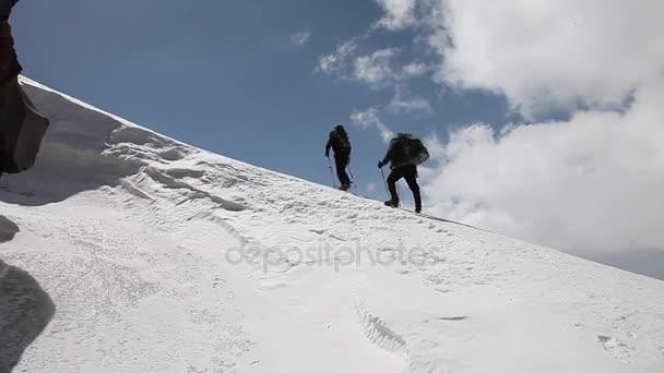 dva horolezci na pozadí oblohy