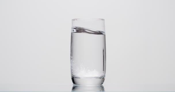 pacient hodí aspirin do sklenice vody na bílém pozadí